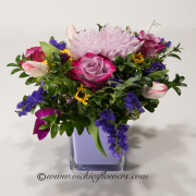 Mothers-Day-Flowers-002 $65 (plus tax and delivery) Mixed Lavender variegated Roses, purple Mums, Tulips, and purple Statice in a keepsake purple glass vase.0