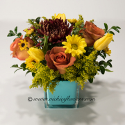 Mothers-Day-Flowers-003 $65 (plus tax and delivery) Mixed bright yellow Tulips, yellow Daisies, Orange Circus Roses in a turquoise keepsake glass vase.