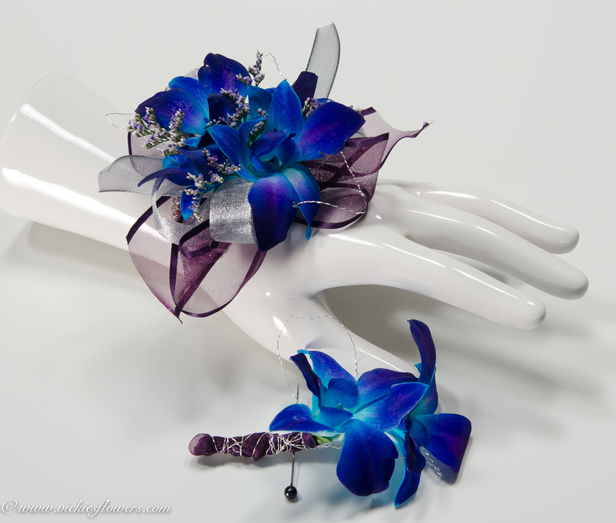 Corsage boutonnieres prom homecoming vickies flowers brighton prom 026 35 boutonniere 20 plus tax and delivery blue orchid wrist corsage with matching blue orchid boutonniere wrapped with purple lace ribbon izmirmasajfo Gallery