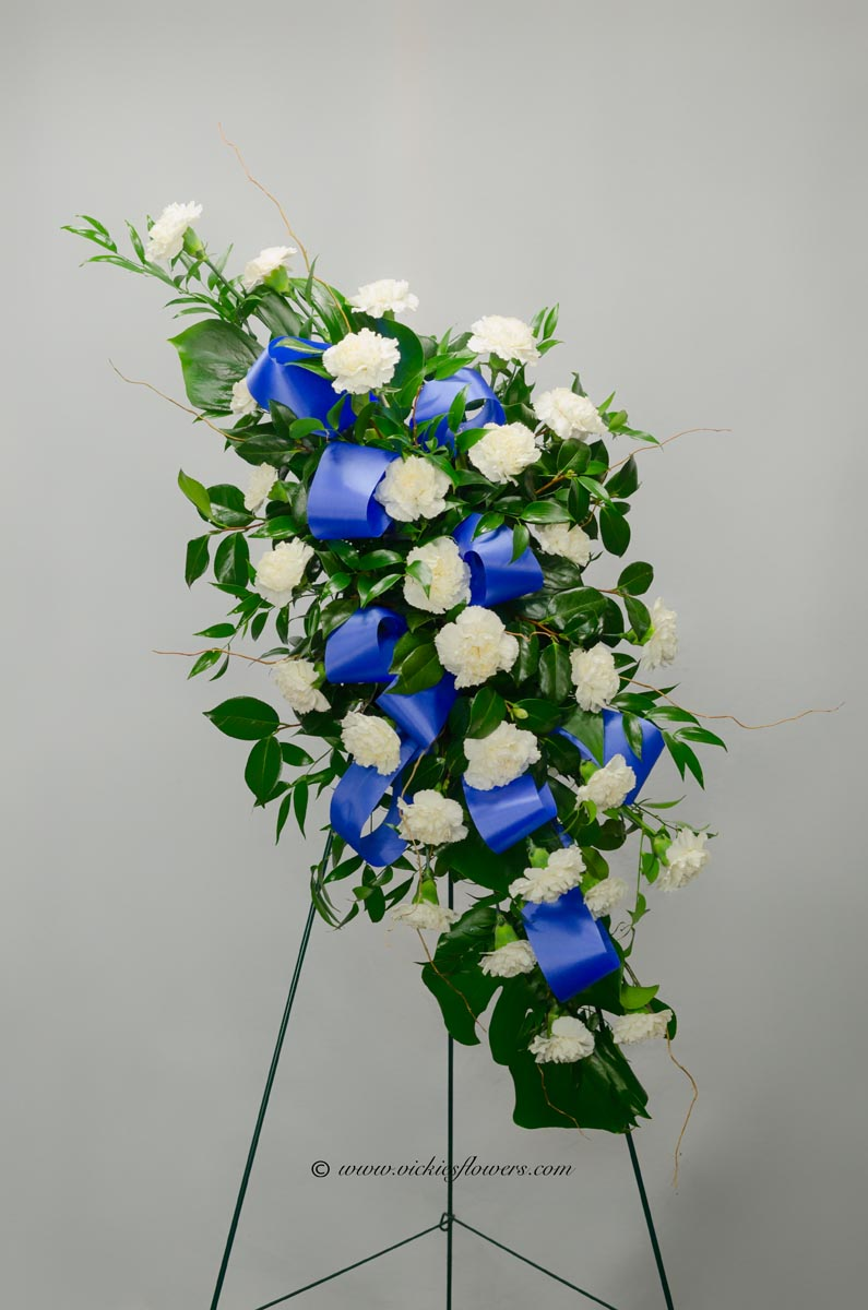 Funeral crosses standing sprays vickies flowers brighton co standing funeral spray 005 125 plus tax and delivery classic flowing white standing spray made with white carnations and decorated with blue ribbon and izmirmasajfo