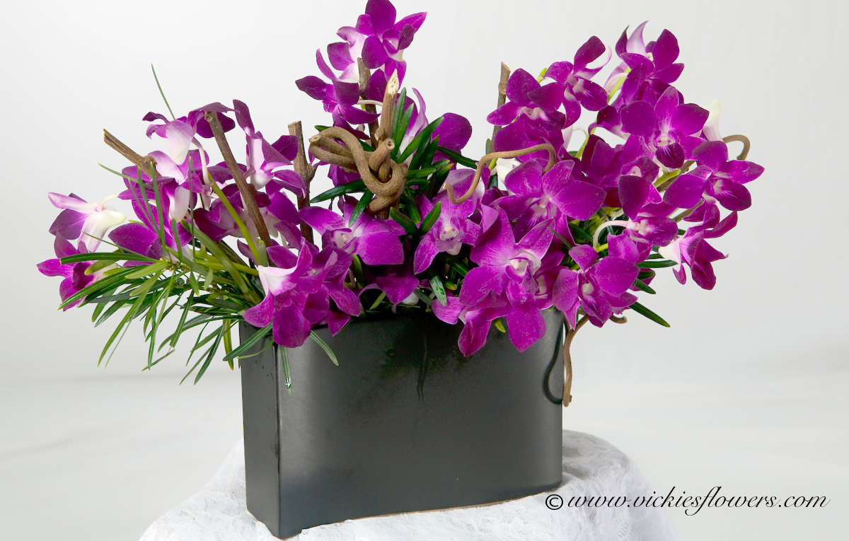 Ikebana Oriental Flowers IB - 017 $110 (plus tax and delivery) Purple Orchids and Podiocarpus with Kiwi branches in black stone container.