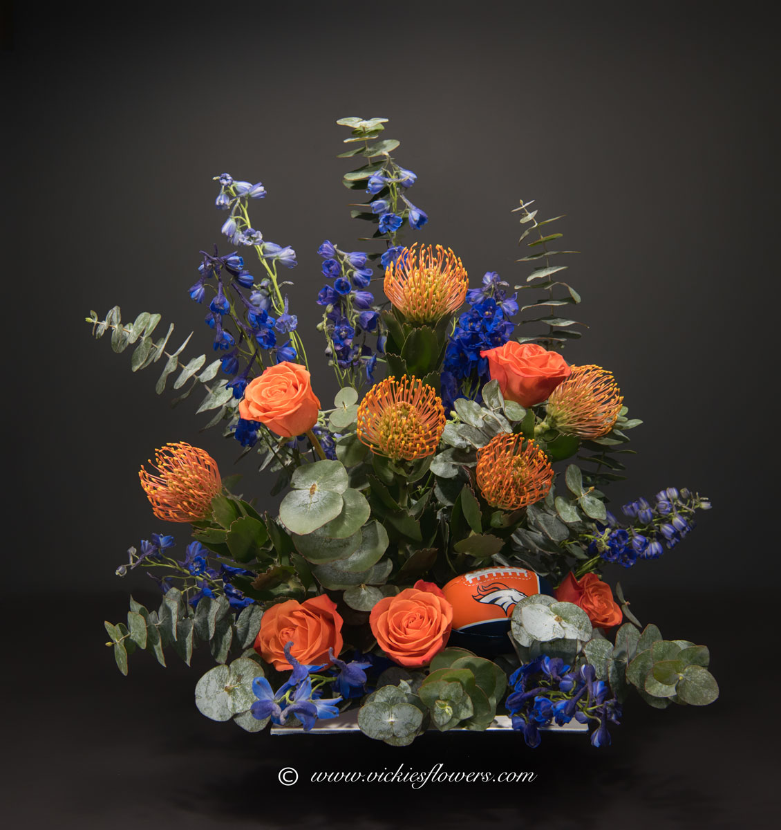 Broncos harley funeral flowers vickies flowers brighton co florist unique themed sympathy 032 150 plus tax and delivery broncos red and orange themed sympathy with football arrangement with orange pin cushion protea izmirmasajfo Choice Image