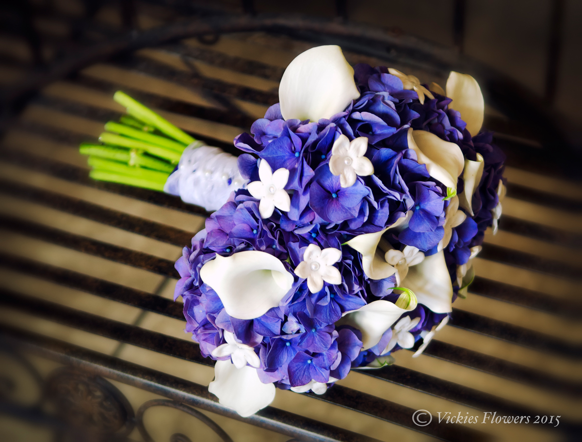 Wedding bouquets vickies flowers brighton colorado florist wb 013 stunning blue and white wedding bouquet flowers include blue hydrangea white calla lilies and white stephanotis the stems are hand tied with izmirmasajfo