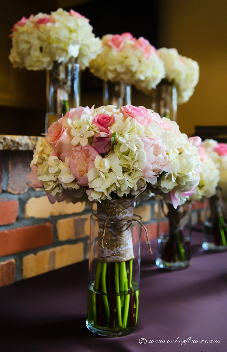 Wedding bouquets vickies flowers brighton colorado florist wb 015 close up photograph of bridal bouquet and bridesmaids bouquets sitting on a brick ledge the bouquets flowers include pink tulips pink roses izmirmasajfo
