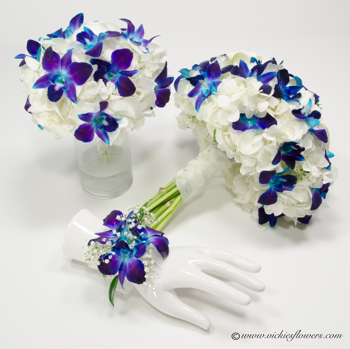 Wedding bouquets vickies flowers brighton colorado florist wb 022 bridal bouquet and bridesmaids bouquet made with white hydrangea and blue dendrobium orchids bouquet is wrapped with white sheer ribbon and izmirmasajfo