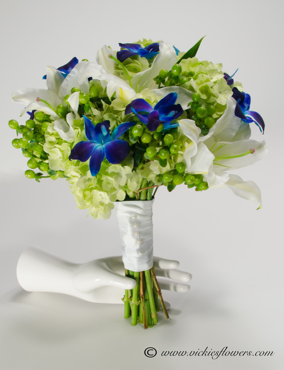 Wedding bouquets vickies flowers brighton colorado florist wb 030 blue orchids white asiatic lilies hypericum and green hydrangea with stems wrapped in white silk ribbon izmirmasajfo