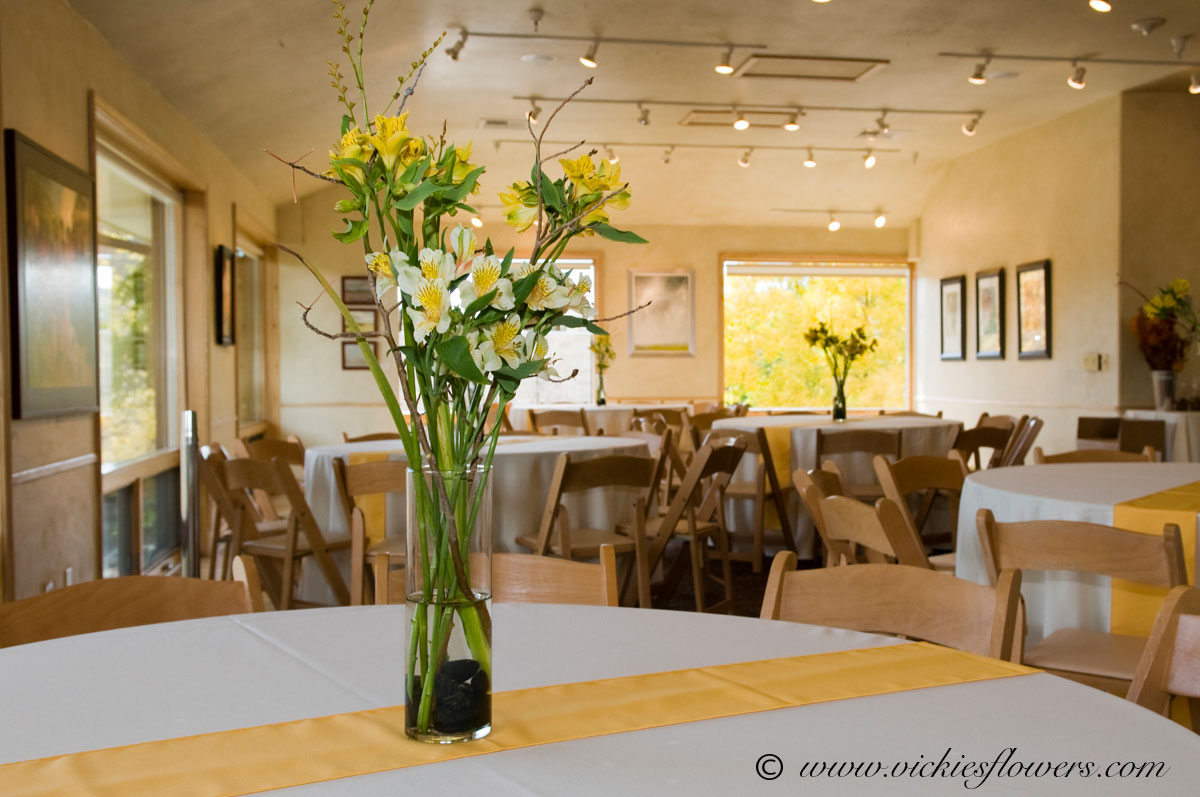Wedding centerpieces vickies flowers brighton co florist wedding centerpieces 023 tall elegant yellow and white centerpiece with lilies and alstroemeria in a cylinder vase accented with black river rocks junglespirit Gallery