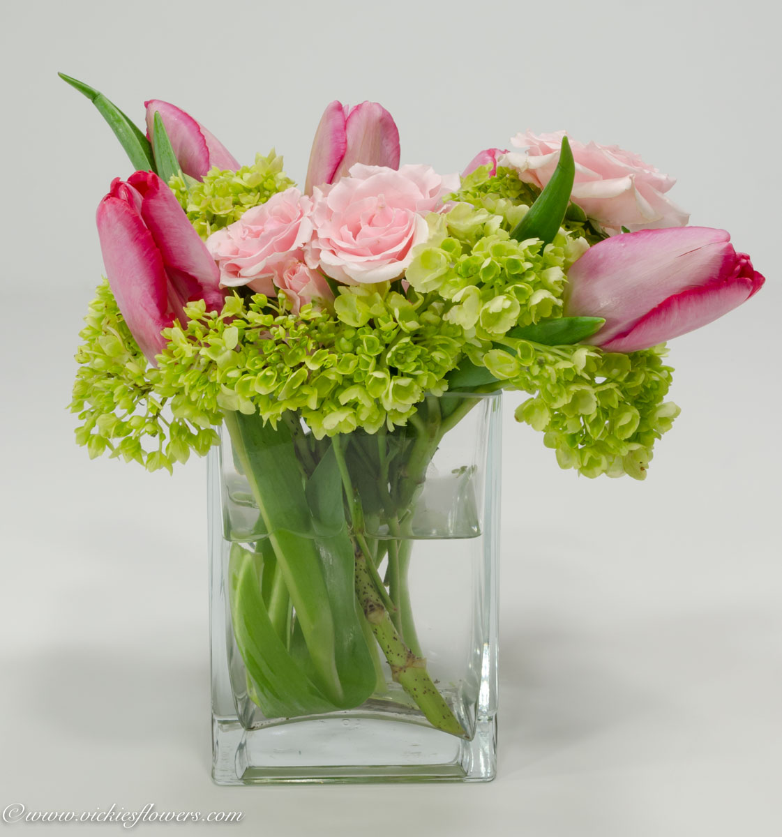 Wedding centerpieces vickies flowers brighton co florist wedding centerpieces 032 beautiful centerpiece with pink tulips and pink roses accented with green hydrangea in a clear square glass vase reviewsmspy