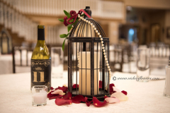 Wedding-Centerpieces-064 Antique lantern laced with pearl necklace, red Rose petals, and red rose topper.