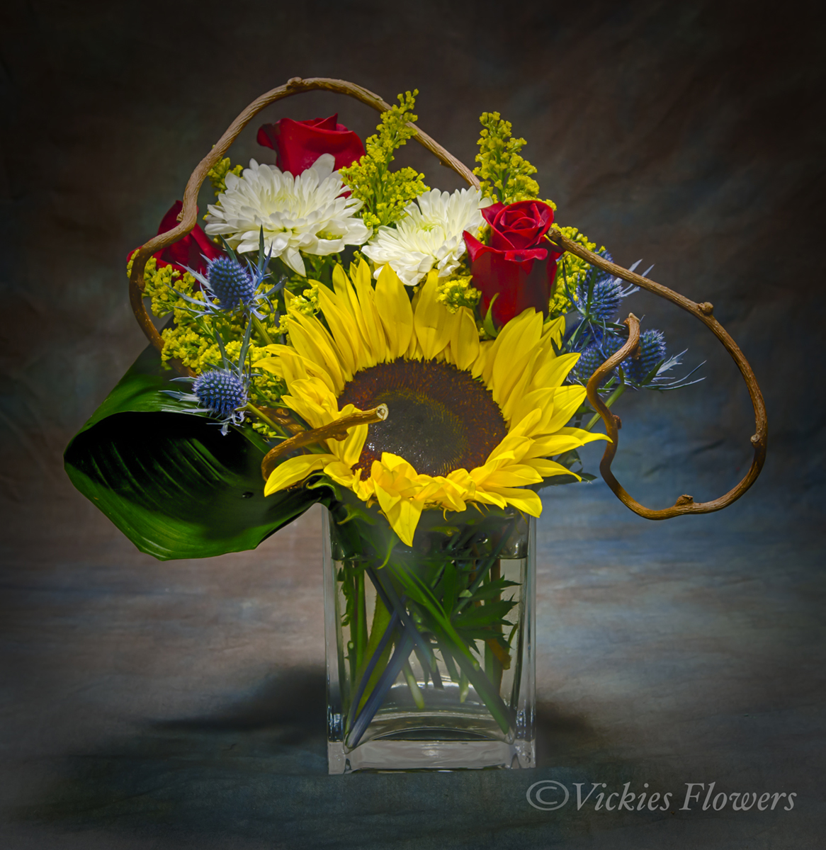 Photograph of Beautiful and brightly colored spring and summer arrangement of Yellow Sunflower, red Roses, Daisies in a clear glass vase.