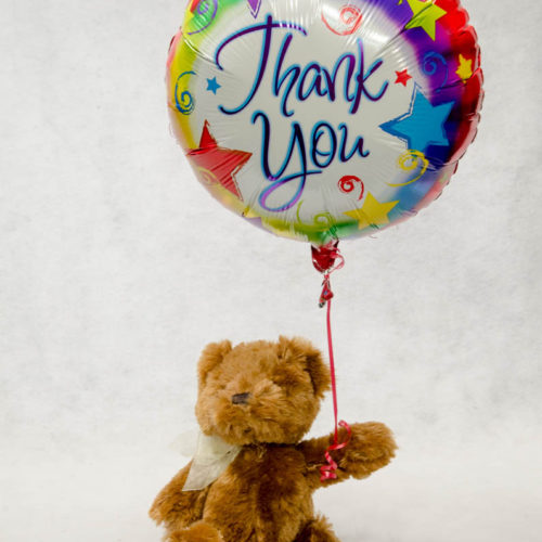 Photograph of teddy bear holding a mylar thank you balloon.