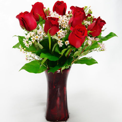 "Photograph of Classically arranged one dozen red Roses with Wax Flower in a red glass vase. Perfect traditional ""I Love You"" bouquet."