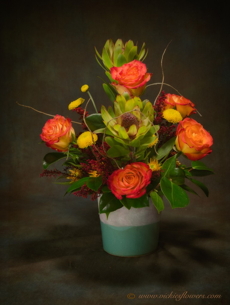 Photograph of Bright and happy orange Circus Roses and Protea with Mums and Curly Willow in unique ceramic vase. Orange and yellow colors great for fall.