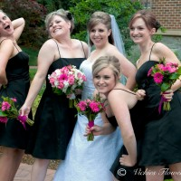 Bride with 4 bridesmaids posing for a fun picture holding their wedding bouquets. Wedding bouquets include pink Gerbera Daisies, White Stalk, White Roses, wrapped with pink and white silk ribbon.