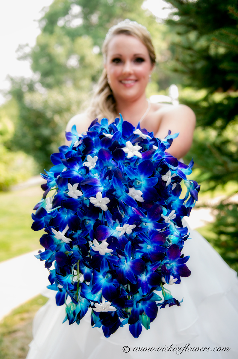 Outdoor photograph of bride holding a purple cascading wedding bouquet. This unique, full and gorgeous bouquet is made with purple Orchids and white Stephanotis.