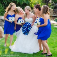 Outdoor photograph of happy smiling bride with bridesmaids. Bride is holding beautiful cascading purple Orchid wedding Bouquet. Bridesmaids are holding white Hydrangea and blue Orchid bouquets.