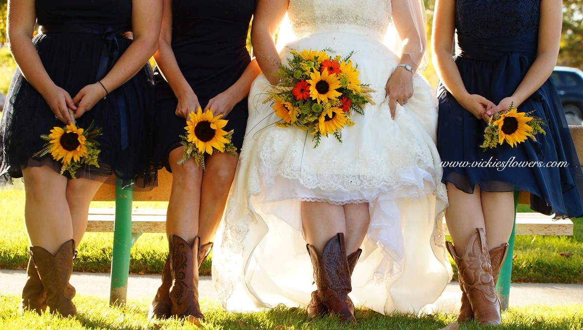 Photograph of western themed wedding with bride in bridal gown with 3 bridesmaids wearing cowboy boots holding wedding bouquets. Wedding Bouquet flowers in yellow Sunflowers, Yellow Solidago, orange Gerber Daisies, Fern, and Wheat Grass.