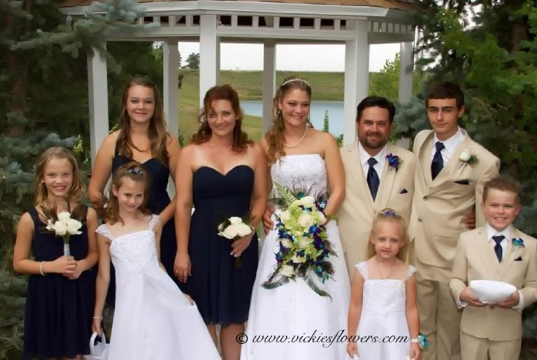 Photograph of Bridal party with bride holding cascading Orchid, Lily, and feather bouquet.