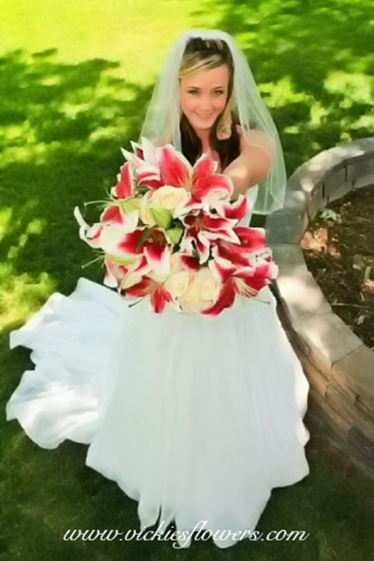 Wide angle image of bride holding a Stargazer Lilly wedding bouquet.