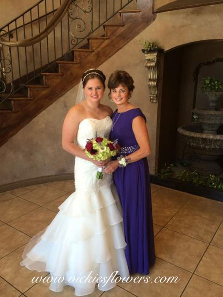 Photograph of Bride with mom holding colorful wedding bouquet with Calla Lilies, Roses, and Hydrangea.