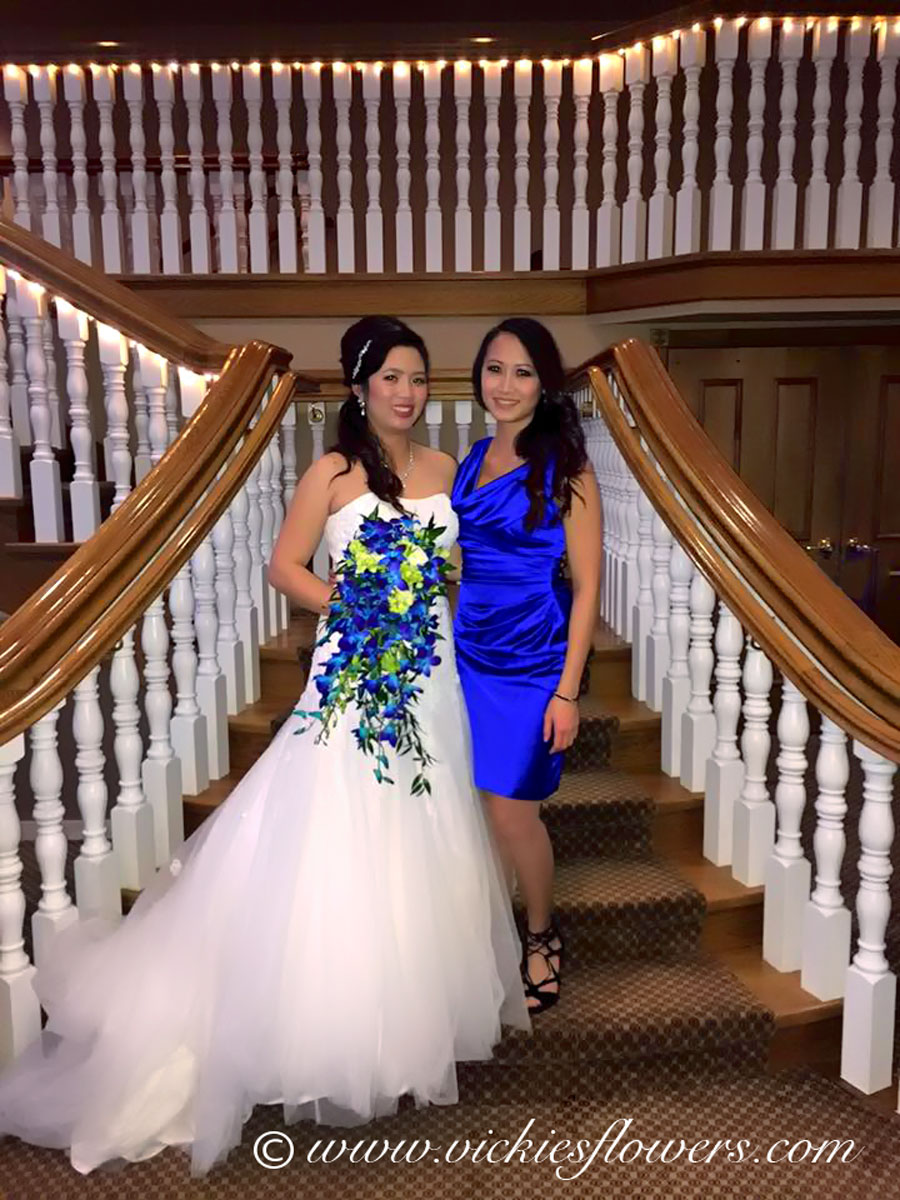Photograph of Bride standing on stairs with maiden of honor holding a cascading blue and green Orchid bouquet.