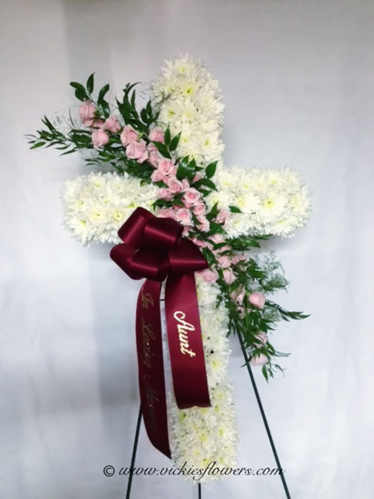 Photograph of Standing funeral spray white cross with white Carnations with pink spray Roses and custom red ribbon.
