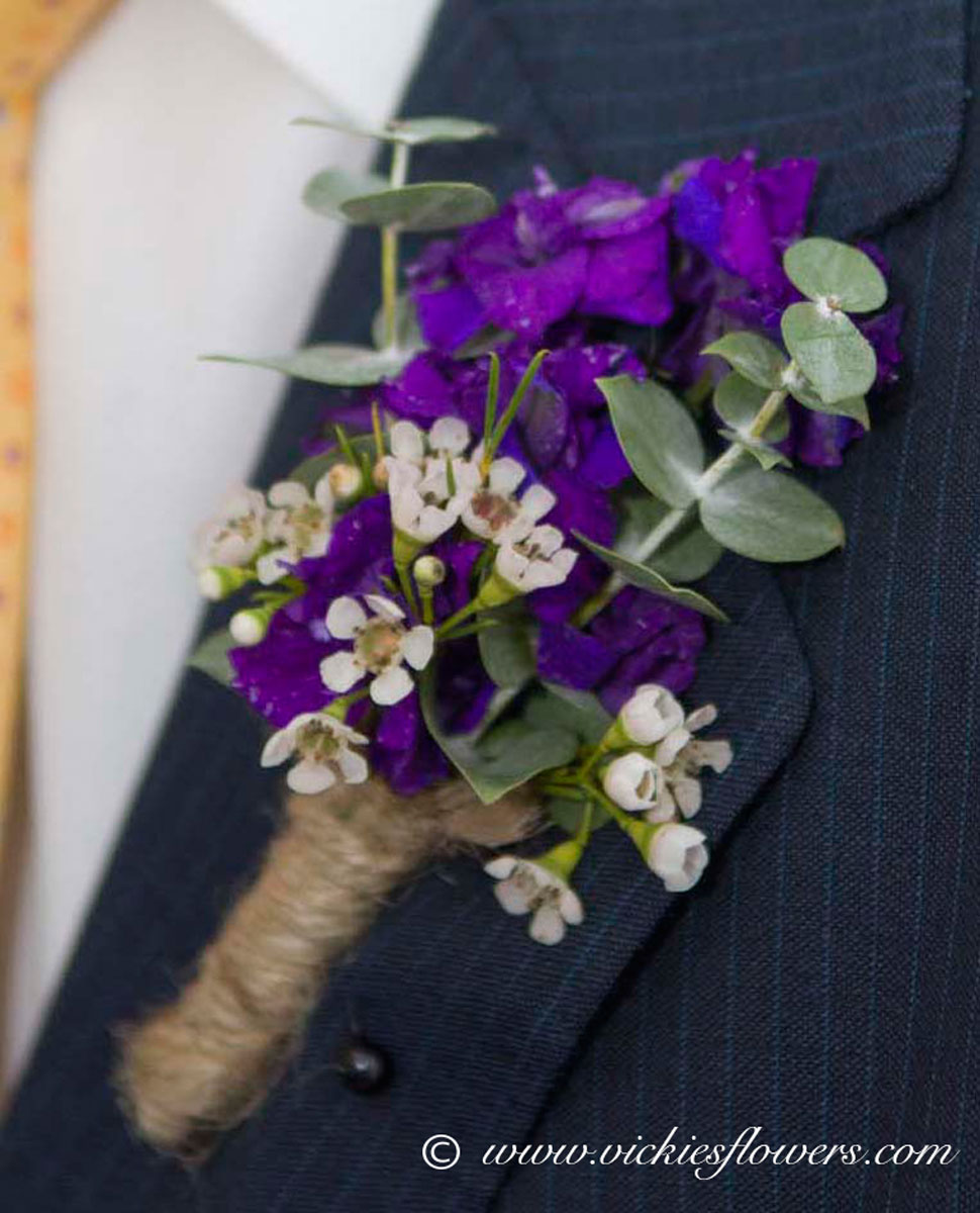 Photograph of boutonniere on men's jacket with Purple Stalk, Wax Flower and Eucalyptus hand tied with twine.