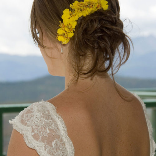 Photograph of bride modeling Yellow Orchid bridal hairpiece.