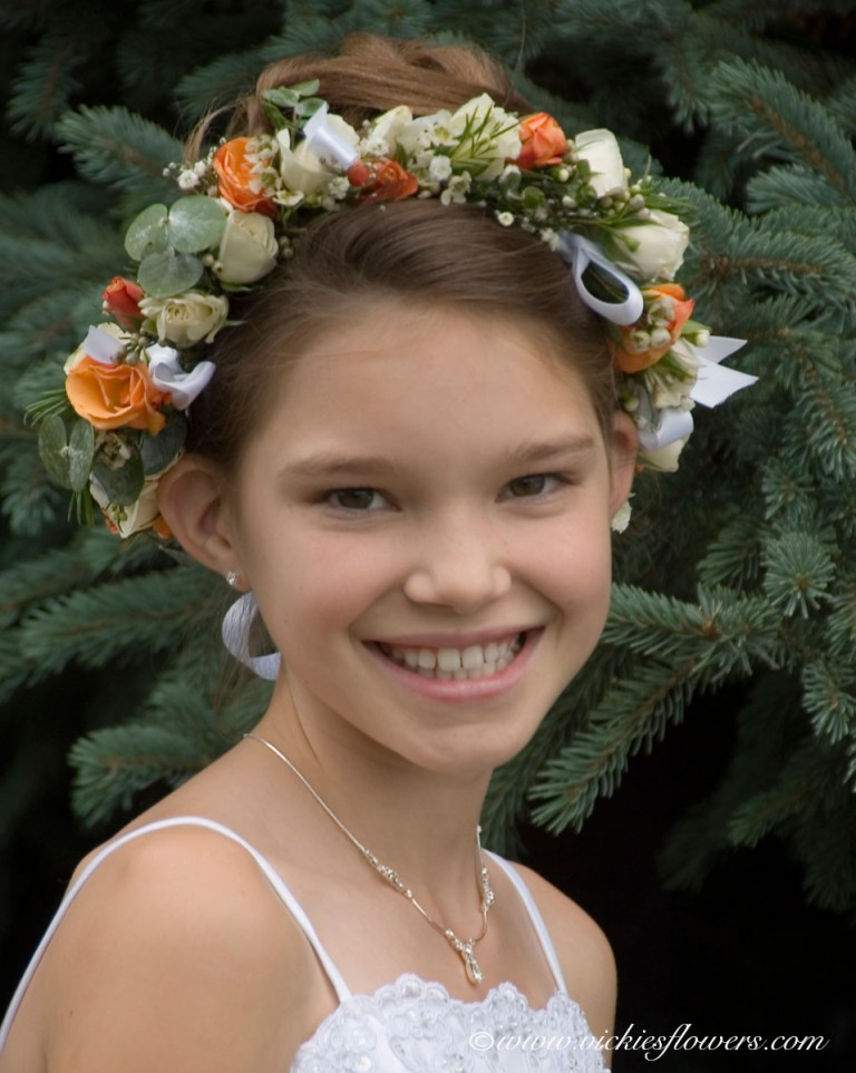 Photograph of flower girl with White and orange Flower Girl hairpiece with Spray Roses, Eucalyptus, and Wax Flower.