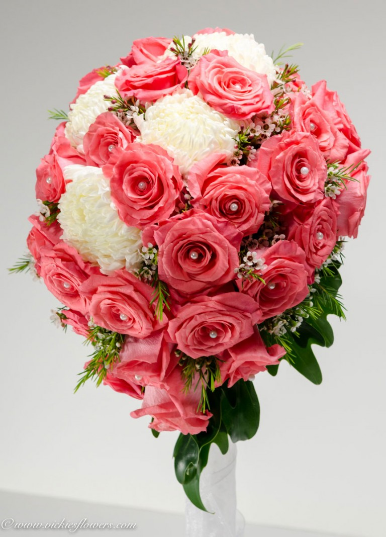 Close up photograph of Cascading pink and white wedding bouquet with white Football Mums, beautiful pink Roses with studded pearl centers, pink Wax flowers, and Juniper. Holder is wrapped with white silk ribbon.