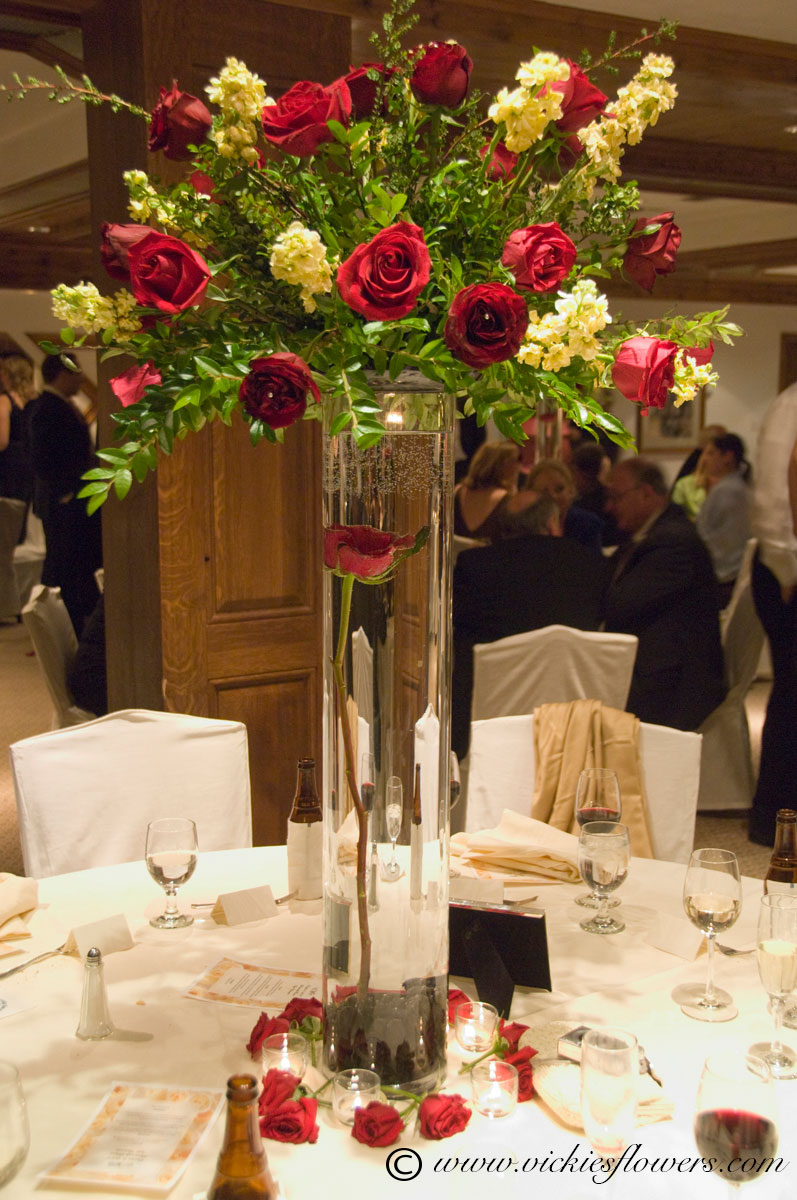 Photograph of Towering and large centerpiece with red Rose submerged in glass cylinder vase topped with a large red Rose and white Orchid topper. Centerpiece is surrounded by red Rose heads and candles.