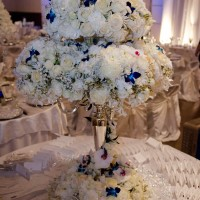 Photograph of Very large and elegant candelabra centerpiece with white Roses, white Orchids, white Hydrangea and accented with blue Orchids mounted on a sliver candelabra.
