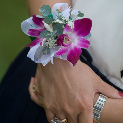 Photograph of white and purple Phalaenopsis Orchid wrist corsage for a wedding with Eucalyptus, white sheer ribbon and pearl wrist band.