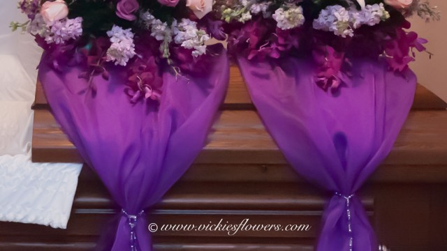 Photograph of Beautiful classy purple 2 tier casket spray $600 as show. Pink and purple Roses, blue Hydrangea, Stargazer Lilies. Includes purple sheer tied with jewels.