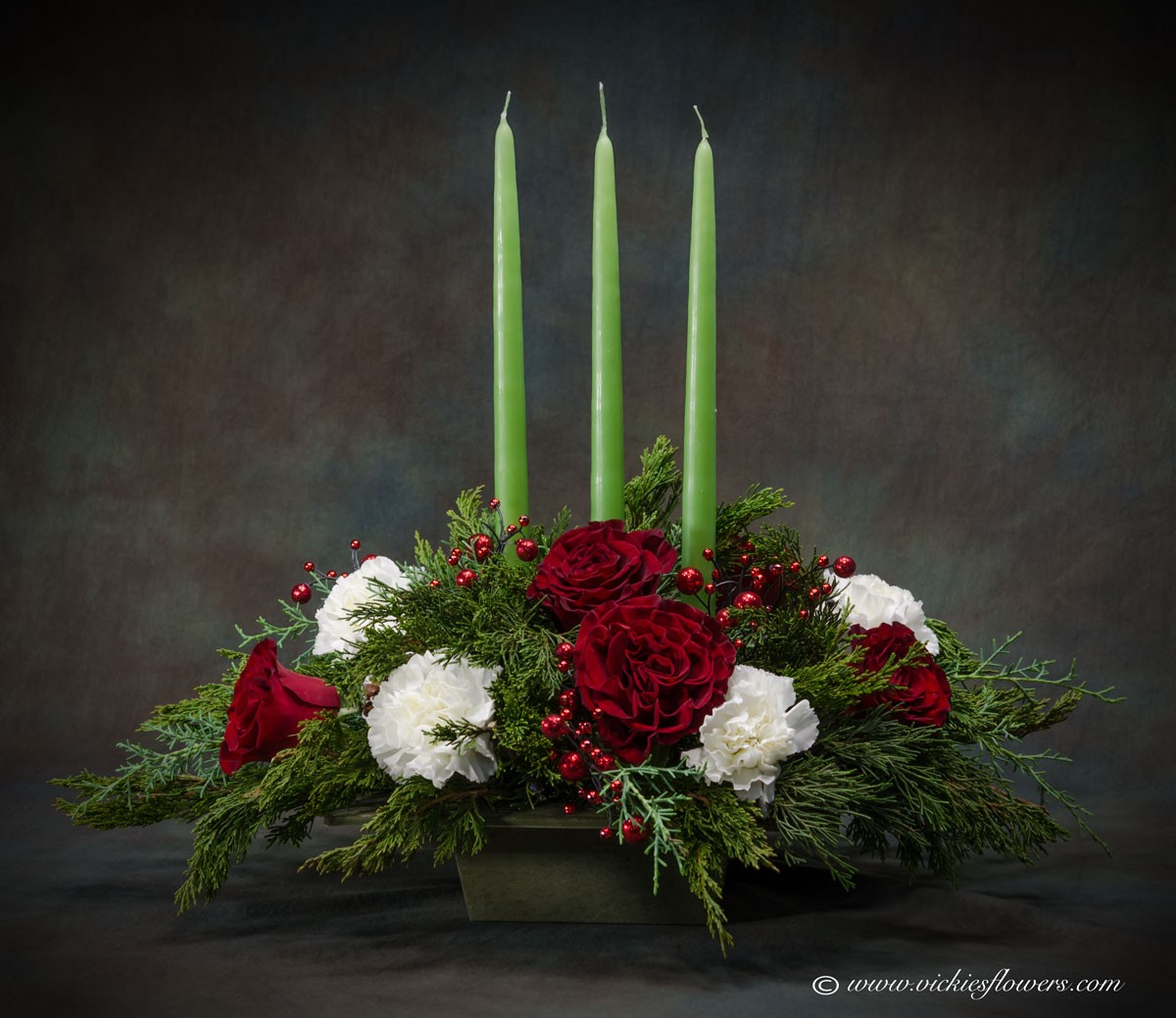Photograph of We custom make every flower arrangement in house to your specifications. Beautiful holiday 3 candle centerpiece, perfect for any Christmas gathering.
