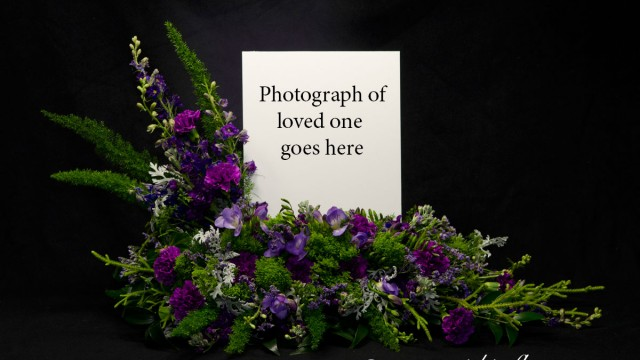 Photograph of Our very popular purple themed cremation with photograph arrangement. Flowers surround picture of your loved one. Price does not include printed image. We can also Photoshop, print and mount images for an additional fee. See our funeral printing services page. Flowers in this arrangement include purple Snap Dragons, purple Iris, purple Carnations, and unique assorted greenery.