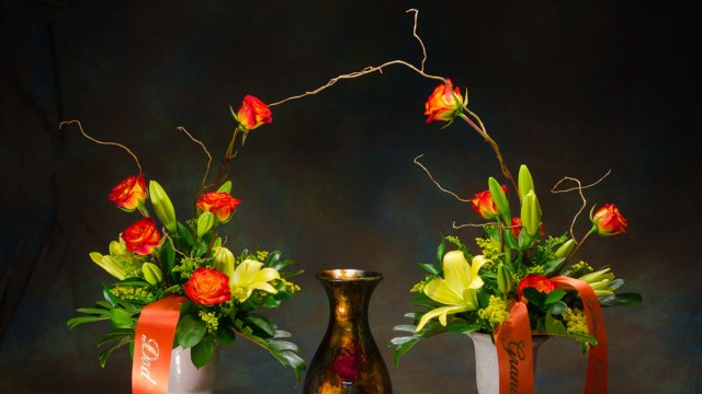 Photograph of Classy arching urn arrangement with two vases of flowers connected with a Curly Willow Arch. Each vase of flowers contains yellow Lilies, orange Roses, and yellow Solidago. Includes custom message with your personal message.