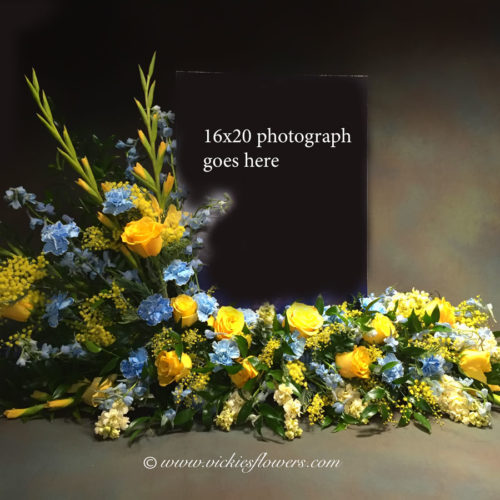 Photograph of Our very popular yellow and blue cremation with photograph arrangement. These beautiful arrangement have flowers that surround the image of your loved one. Price does not include printed image. We can also Photoshop, print and mount images for an additional fee. See our funeral printing services page. This cremation arrangement includes yellow Snap Dragons, yellow Roses, blue Delphinium, yellow Solidago, yellow Stock, and blue carnations.