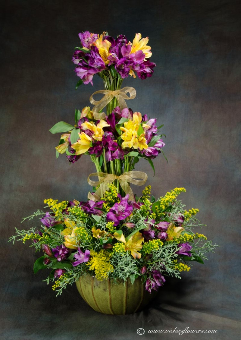Photograph of funeral sympathy flowers Yellow and purple Alstroemeria Topiary with yellow Solidago, with greenery and yellow satin ribbon in a unique ceramic vase.