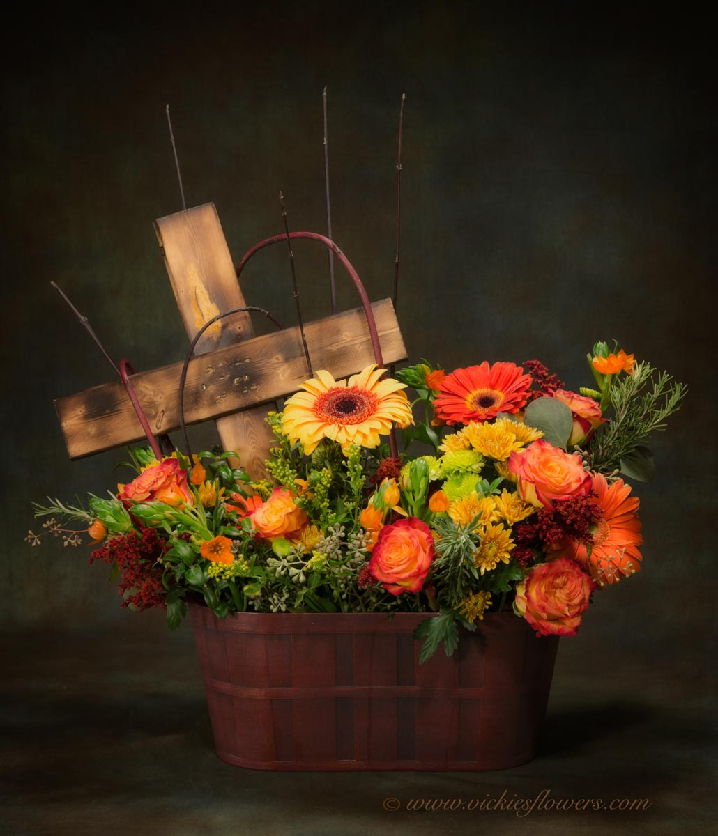 Photograph of funeral sympathy flowers Unique memorial basket of flowers with wooden keep sake cross. Flowers include yellow Gerber Daisies, orange Circus Roses, orange Gerber Daisies, yellow Mums, Protea, Pussy Willow, and mixed greens.