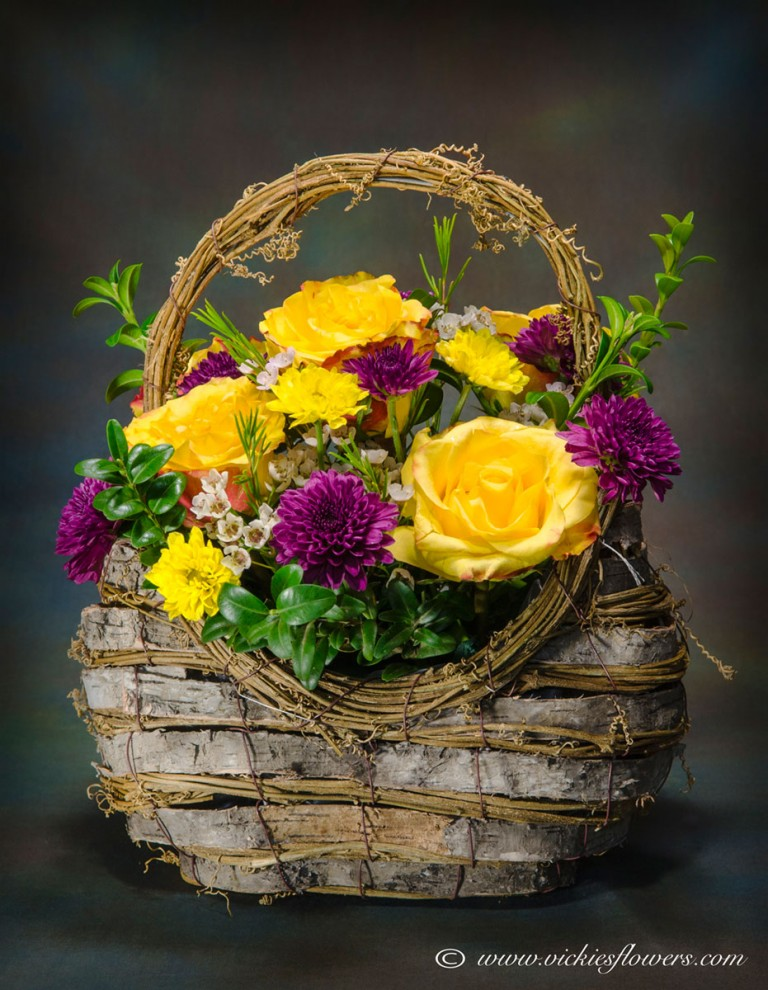 Photograph of Basket with yellow Roses, purple Mums. Wax Flower, and greenery.