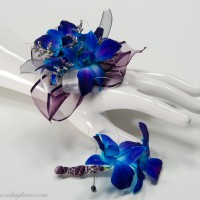 Photograph of Blue Orchid wrist corsage with matching blue Orchid boutonniere. Wrapped with purple lace ribbon, silver wire, and sliver laced ribbon.