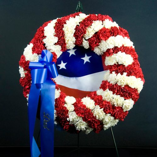 Photograph of Classic circular patriotic or military wreath with red and white Carnations, large blue ribbon and American flag in the center of the wreath. Price includes ribbon and portable metal tripod for display.