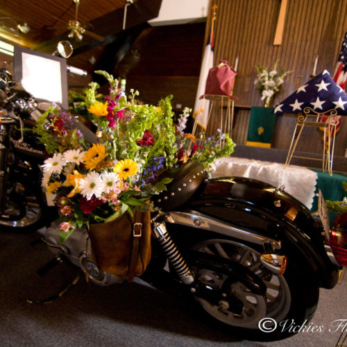 Photograph of Harley Davidson Motorcycle saddle bag funeral flowers tribute. We used the deceased actual Harley Davidson to honor his passion for riding, as well as American flag to honor military service.