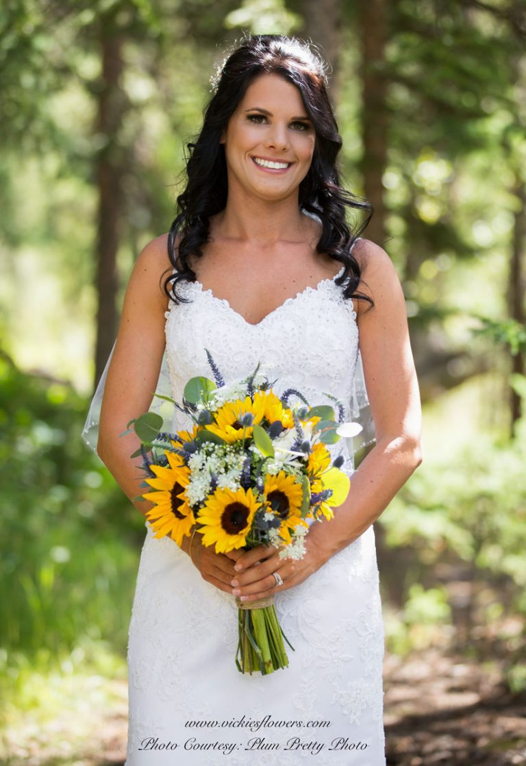 Photograph of very pretty bride holding Beautiful wildflower bridal bouquet with yellow Sunflowers, Eucalyptus, and assorted blue wildflowers.