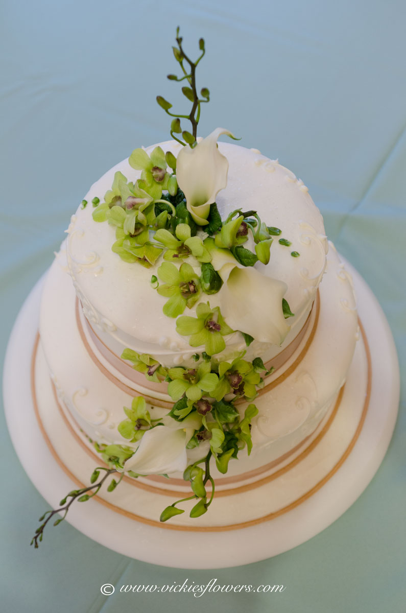 Photograph of Green Cymbidium Orchids and white Calla Lilies cascading down a white and gold wedding cake.