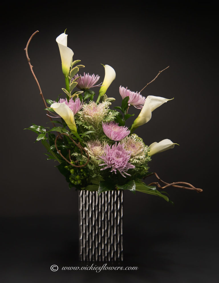 Photograph of Very large unique and stately arrangement with white Calla Lilies, Kale, purple Mums, Kiwi branches, In a unique one of a kind metallic vase.