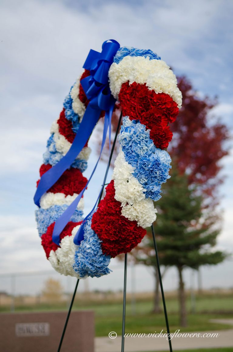 Photograph of Patriotic red, white, and blue Carnation military wreath accented with blue ribbon.
