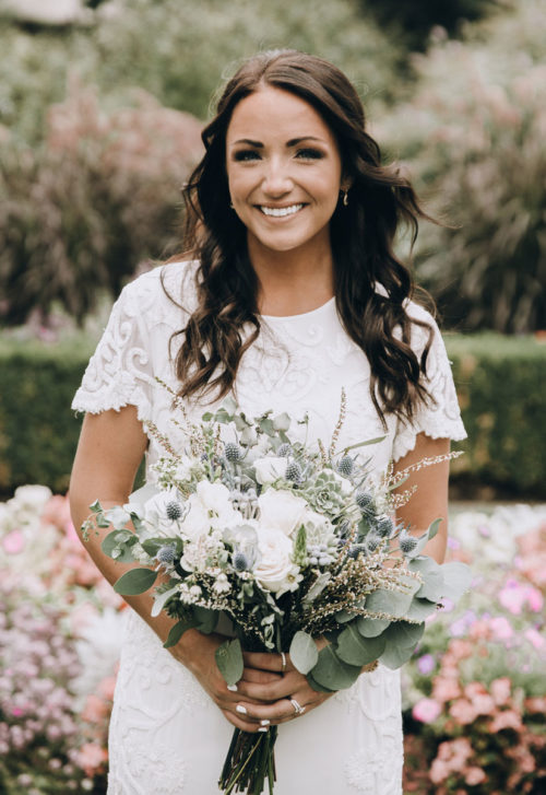 bride holding bridal white bouquet made with white garden Roses, succulents, eucalyptus, and blue thistle, eryngium
