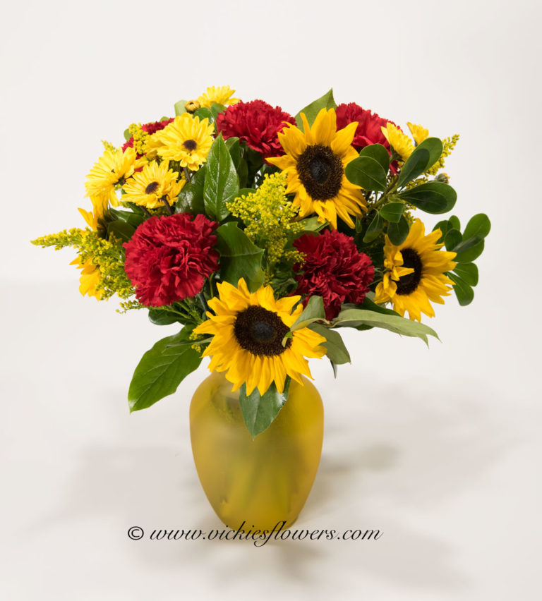 Picture of Sunflower bouquet with red Carnations in yellow frosted glass vase. Vickies Flowers, Brighton Co florist.